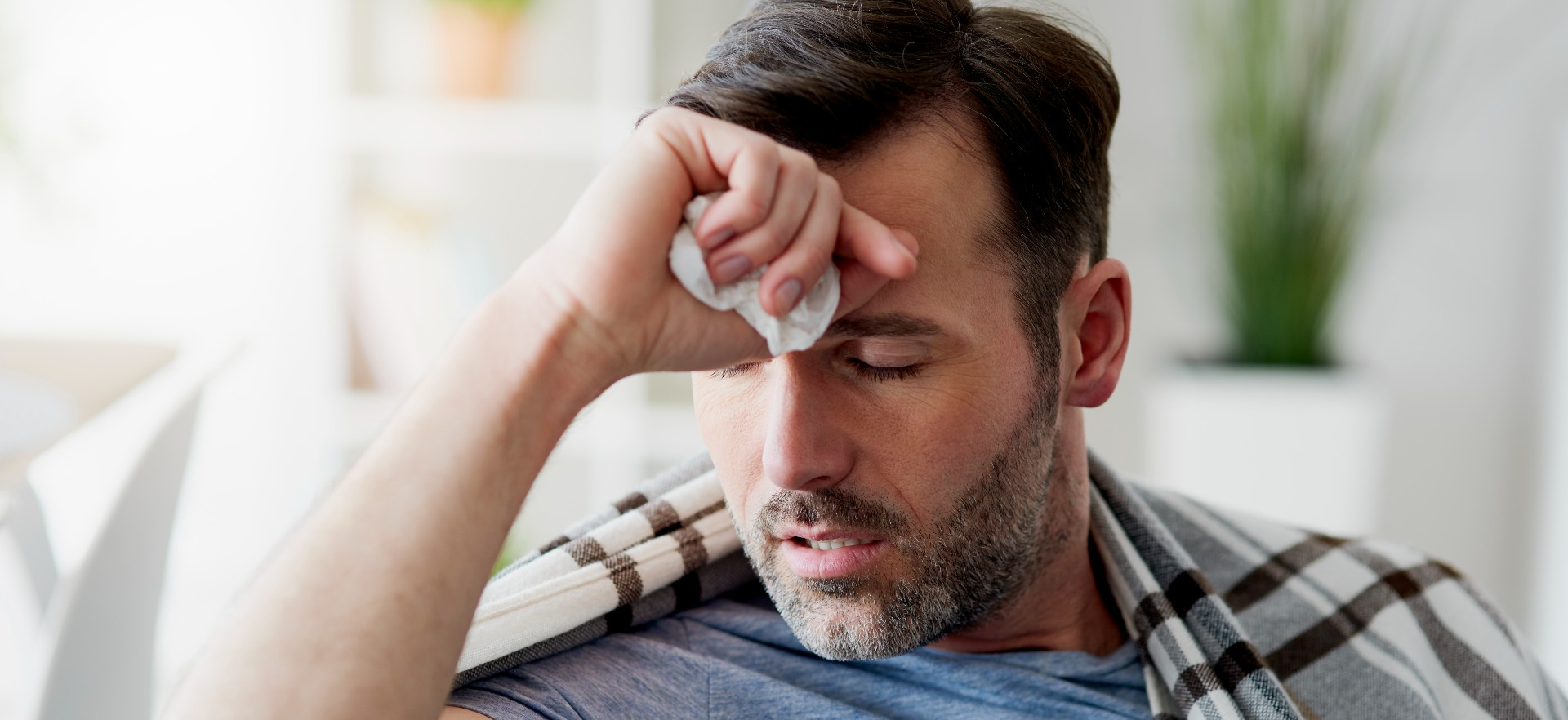 Man with his hand to his head who is not feeling well