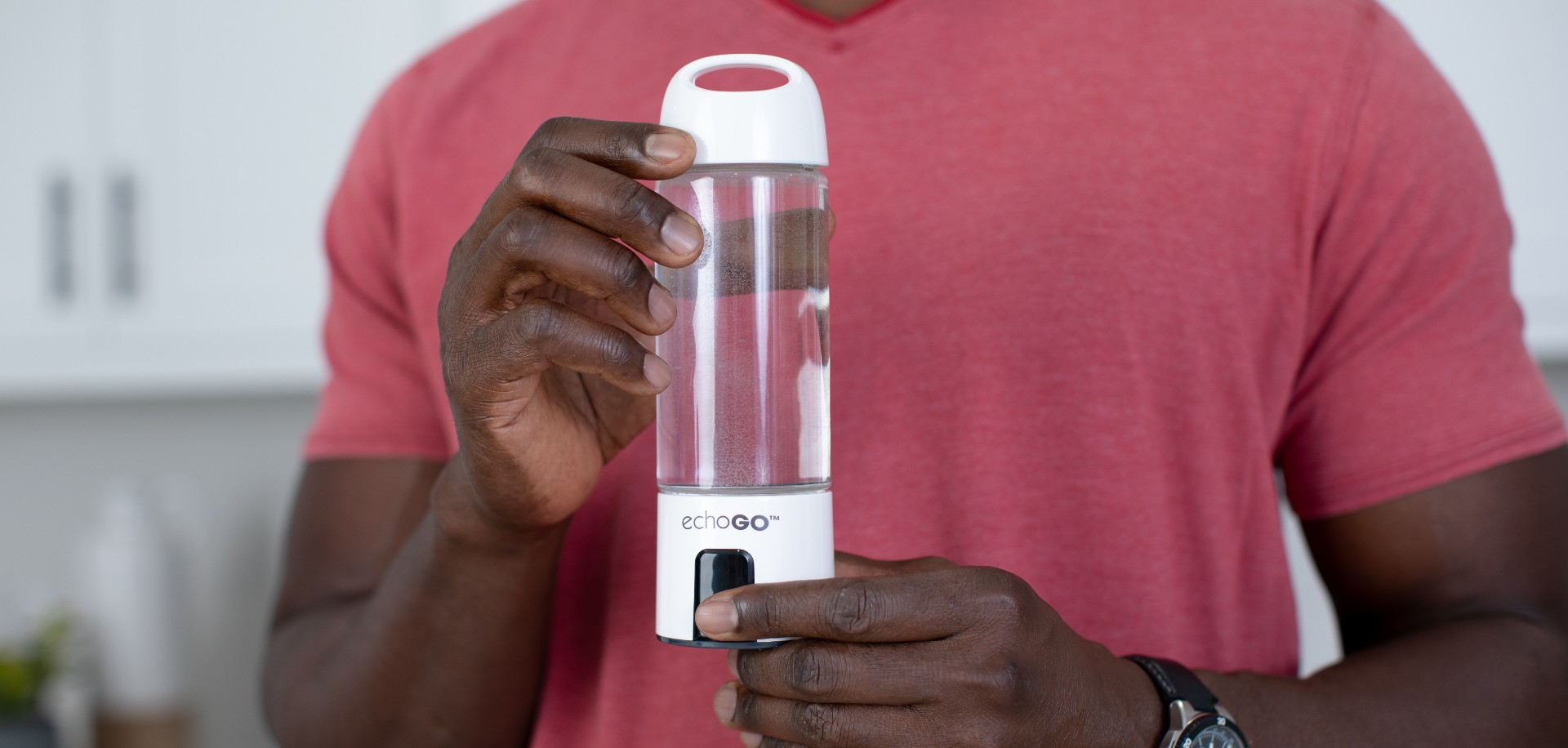 Close up of a man holding the Echo Go hydrogen water bottle