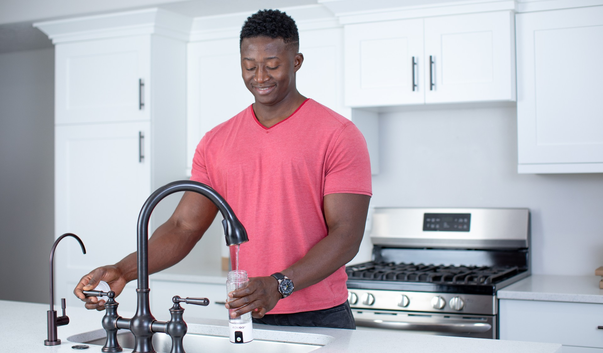 Man filling up the Echo Go hydrogen water bottle at his kitchen sink