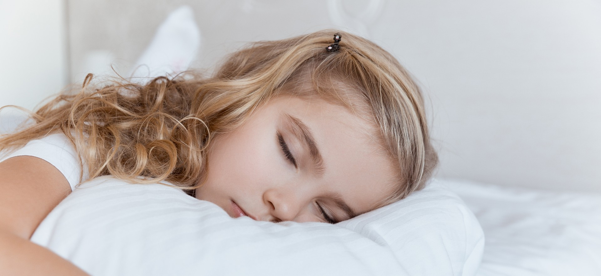 Young girl sleeping on a white pillow at home