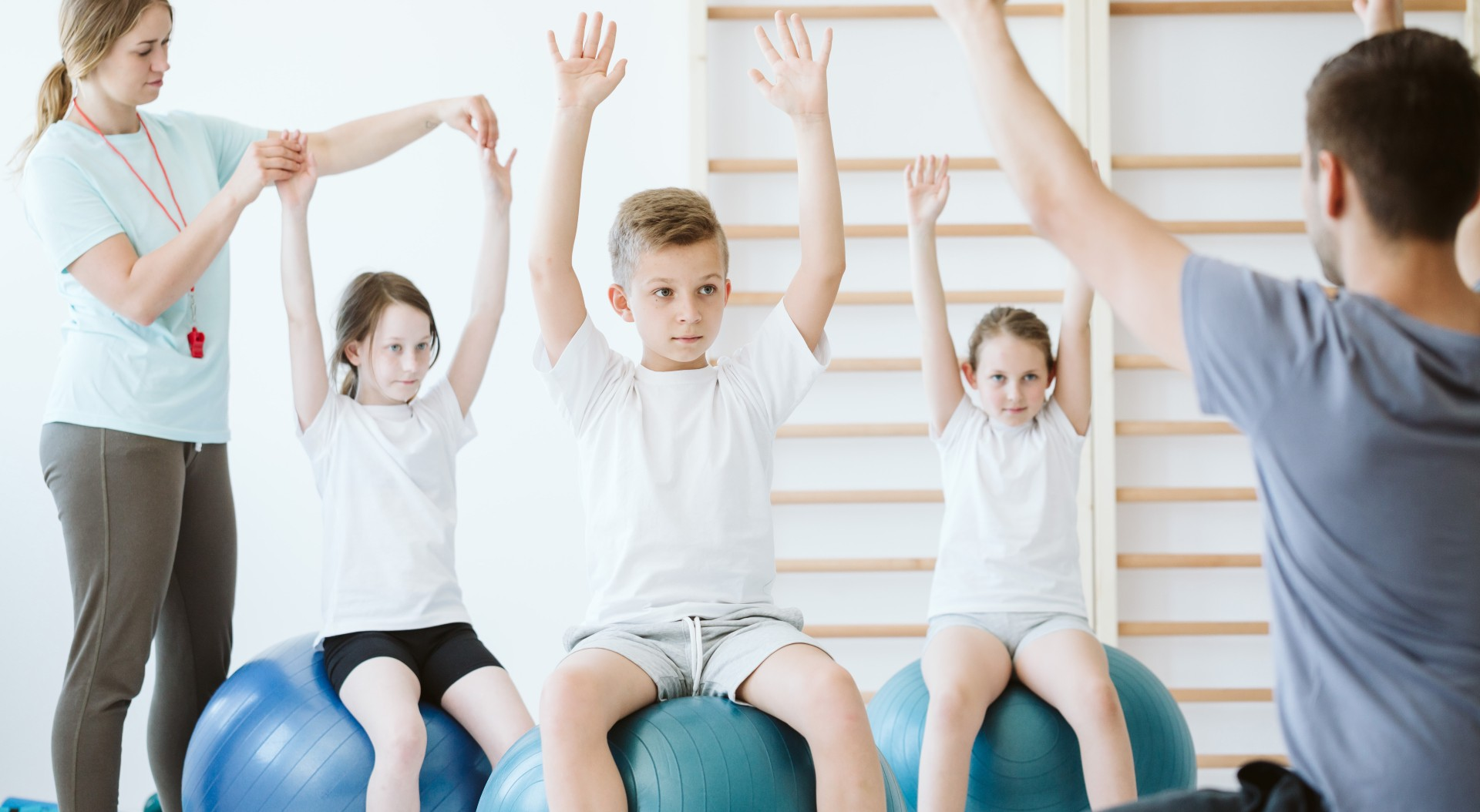 Kids stretching during a P.E. class in a gym