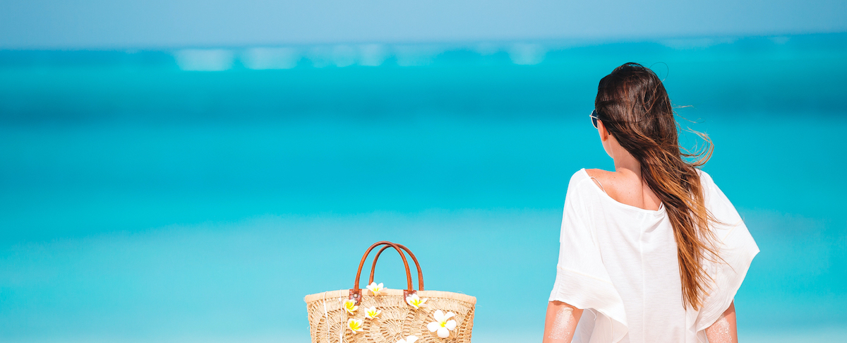Girl looking at the ocean with handbag nearby