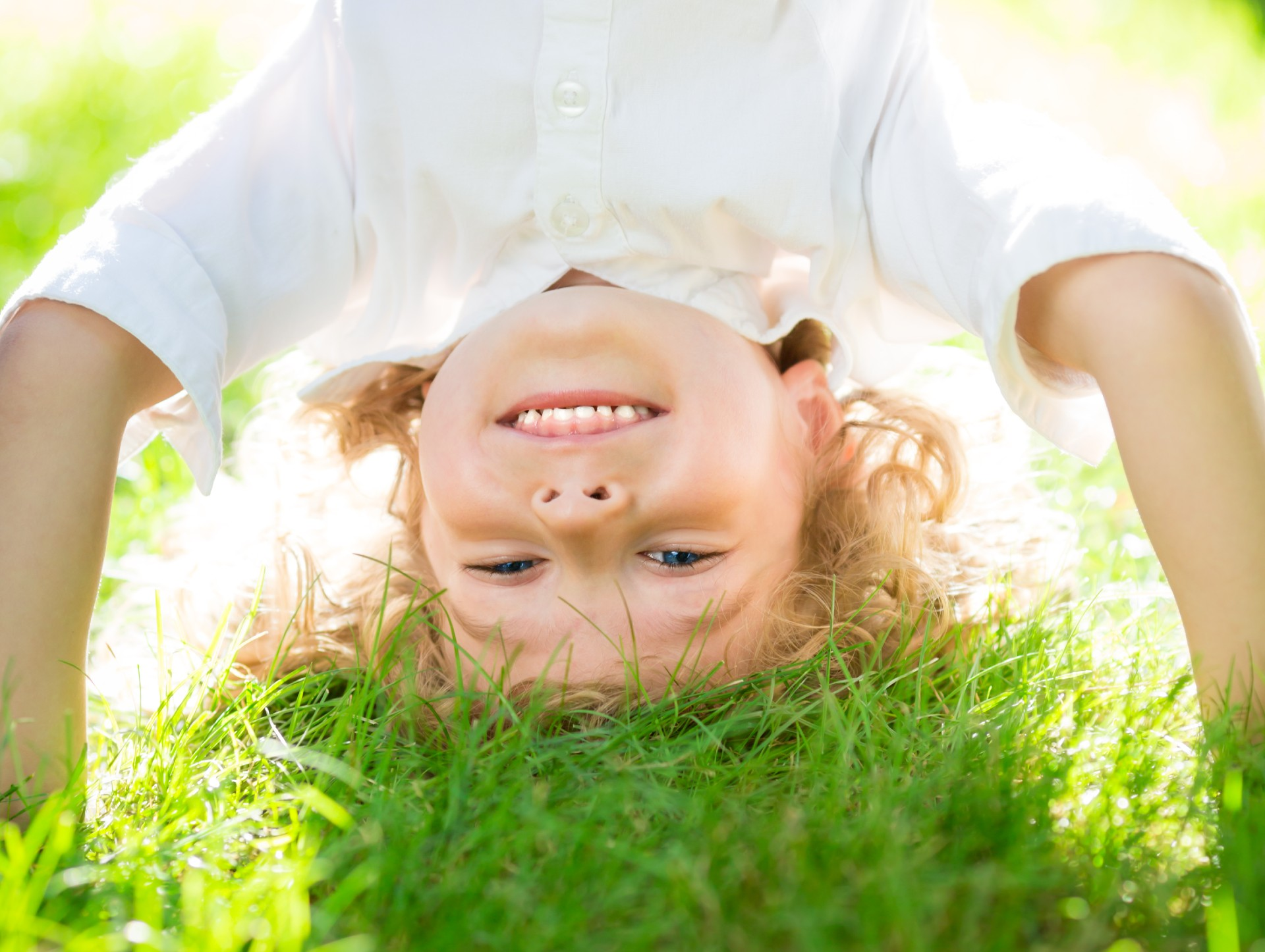 active little boy playing outside on grass