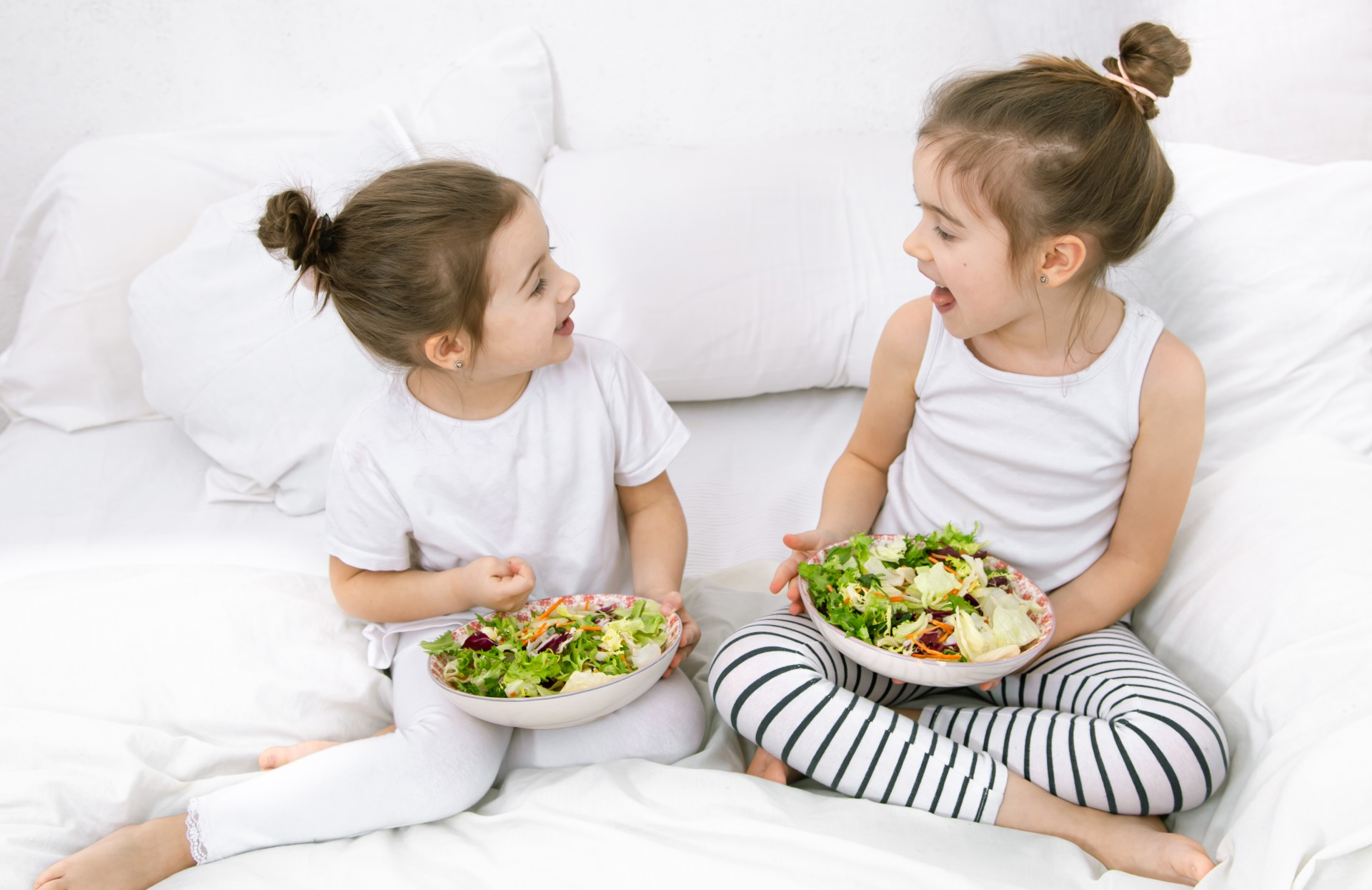 children eating healthy foods on a bed