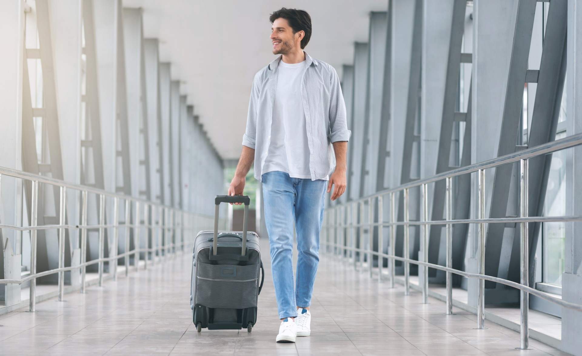 man walking in an airport with a suitcase
