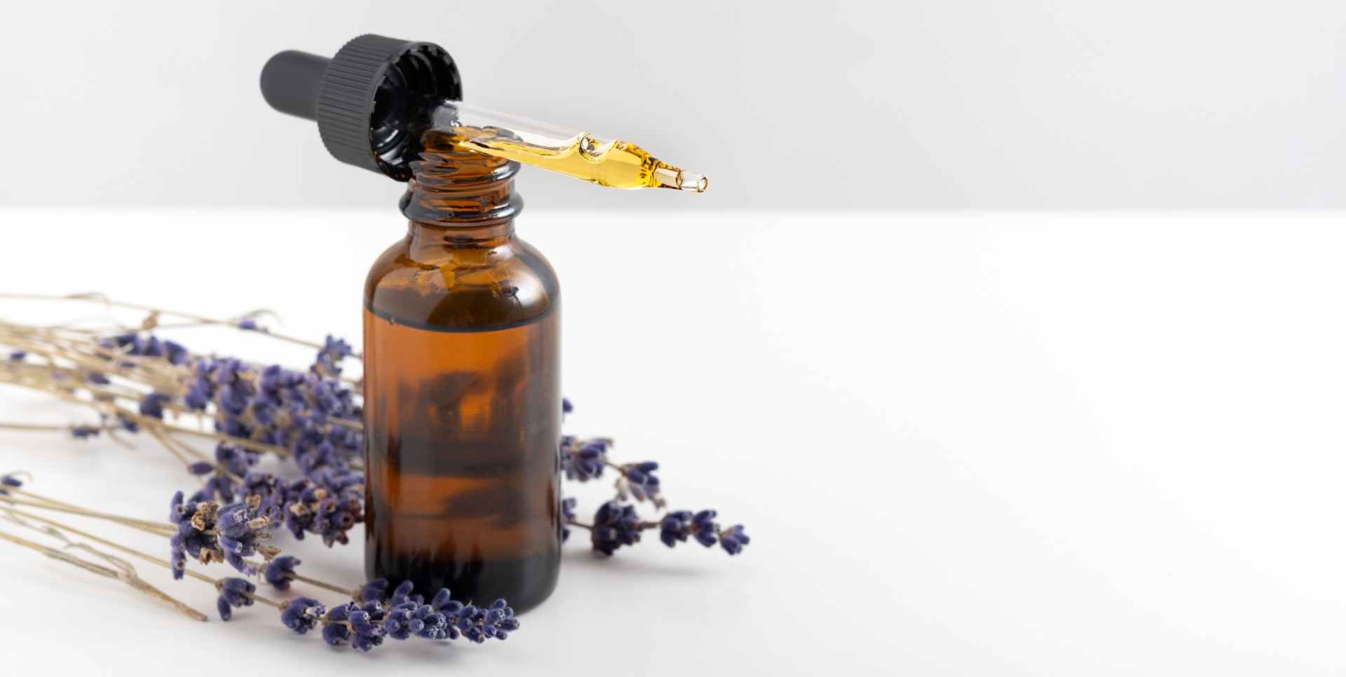 Essential oil bottle with lavender branches near by